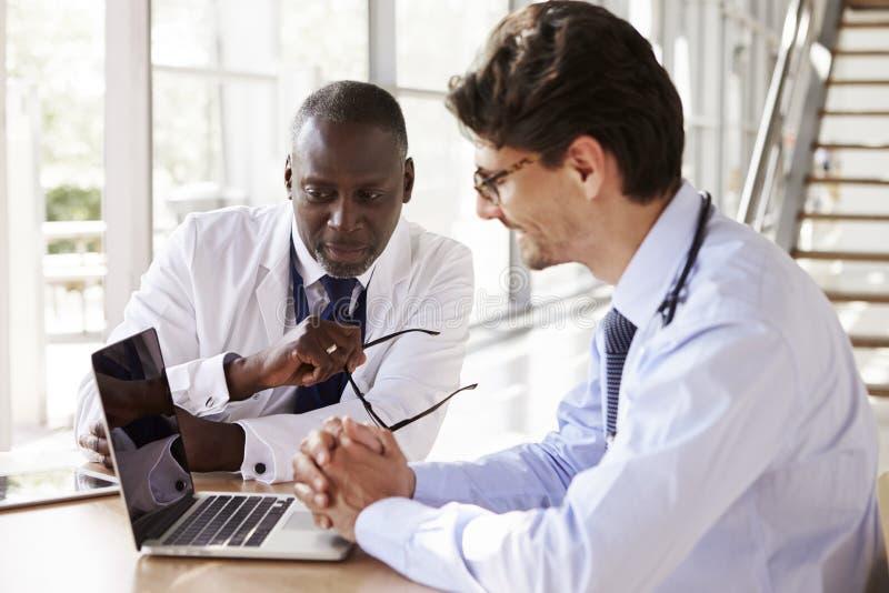 Dois trabalhadores superiores dos cuidados médicos na consulta usando o portátil fotos de stock