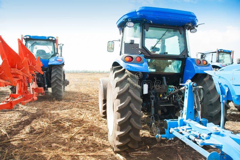 Dois tratores azuis no campo vazio imagem de stock