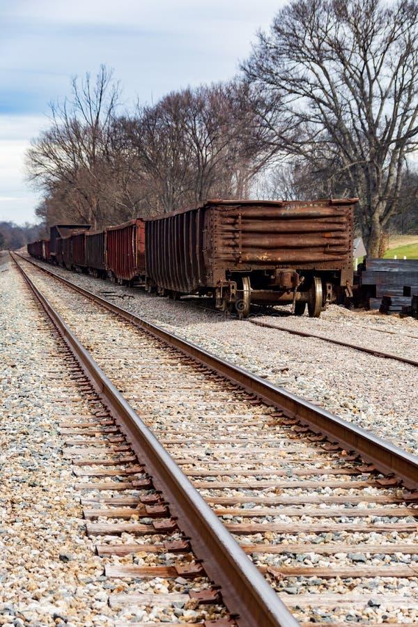 Dois trilhas de estrada de ferro e carros de trilho que viajam à distância imagens de stock royalty free