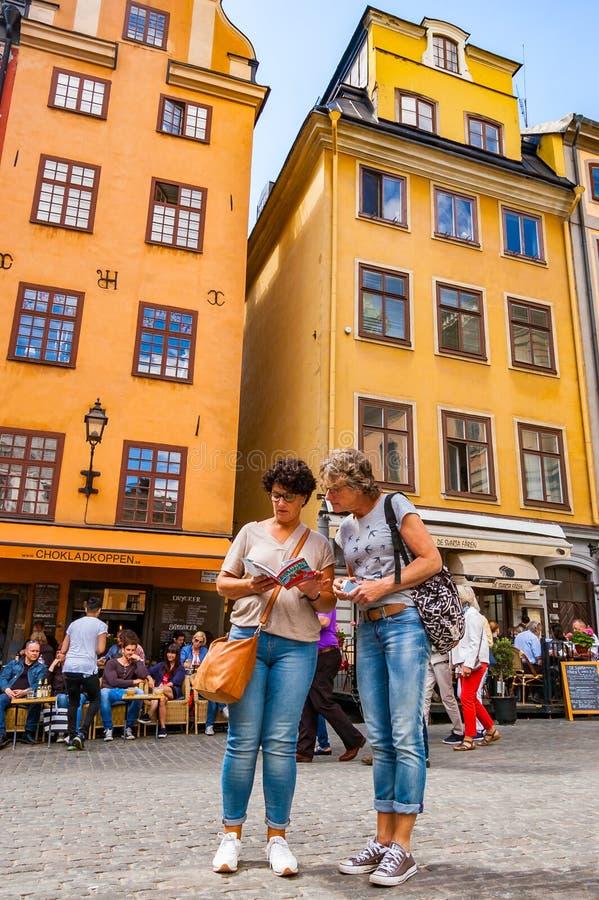 Dois turistas das mulheres que verificam o guia na rua medieval acolhedor com os povos de passeio, fachadas amarelas das construç imagens de stock royalty free