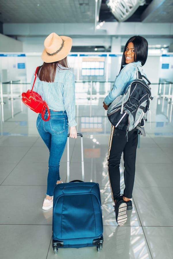 Dois turistas f?meas com bagagem no aeroporto imagem de stock