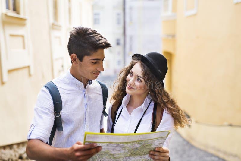 Dois turistas novos com mapa e câmera na cidade velha imagens de stock royalty free