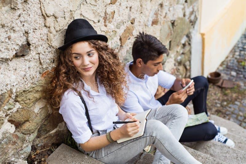 Dois turistas novos com o smartphone na cidade velha imagens de stock royalty free