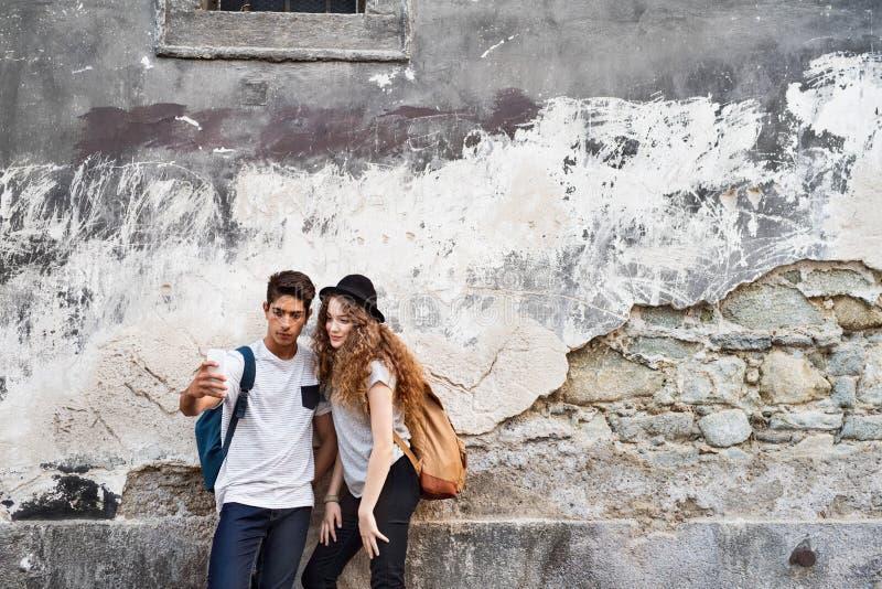 Dois turistas novos com smartphone e câmera imagens de stock