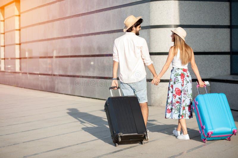 Dois turistas novos felizes que andam em conjunto longe da câmera, puxando malas de viagem fotos de stock royalty free