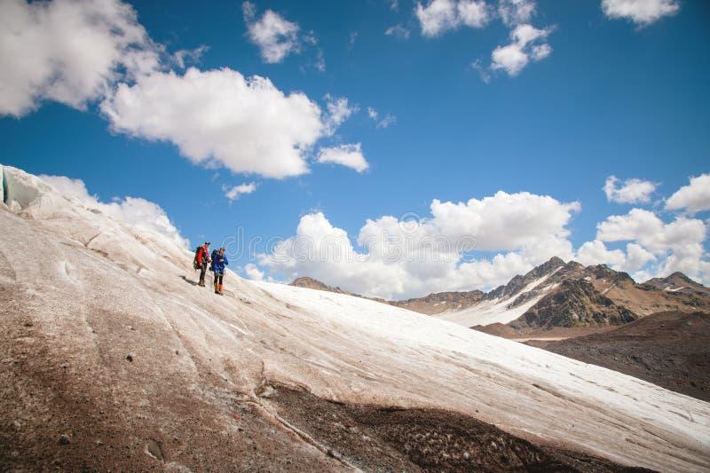 Dois turistas, um homem e uma mulher com trouxas e gatos em seus pés, suporte no gelo no fundo do fotos de stock