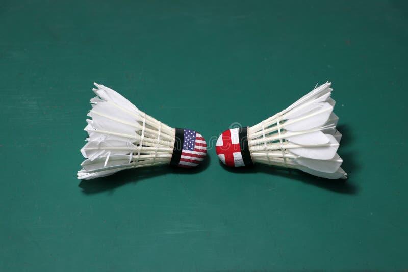 Dois usaram petecas no assoalho verde da corte de badminton com para dirigir-se Uma cabeça pintada com bandeira de América e uma  foto de stock royalty free