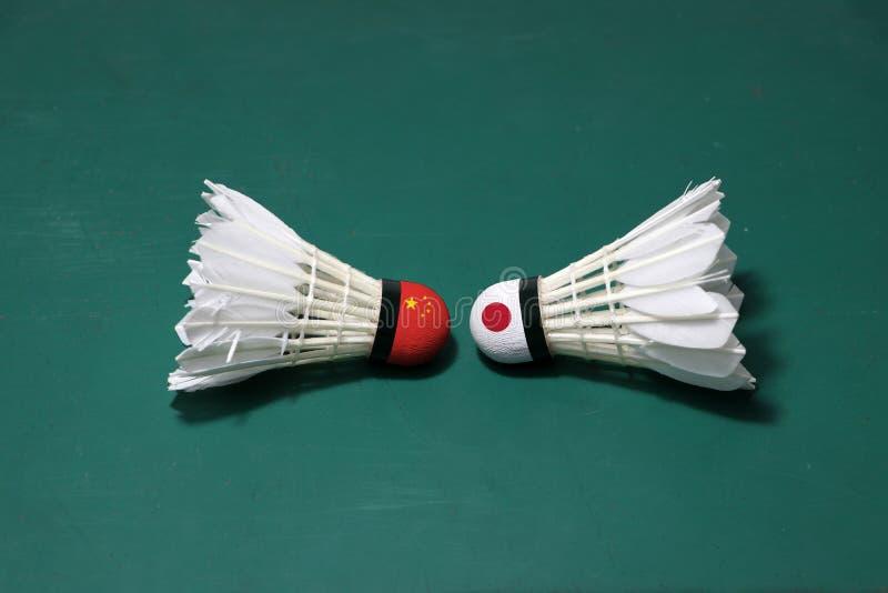 Dois usaram petecas no assoalho verde da corte de badminton com para dirigir-se Uma cabeça pintada com bandeira chinesa e uma cab fotos de stock