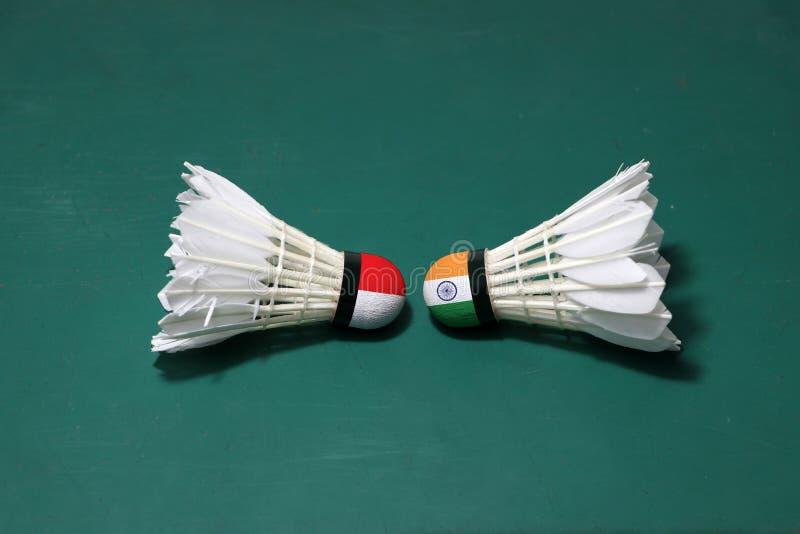 Dois usaram petecas no assoalho verde da corte de badminton com para dirigir-se Uma cabeça pintada com bandeira e uma de Indonési fotos de stock