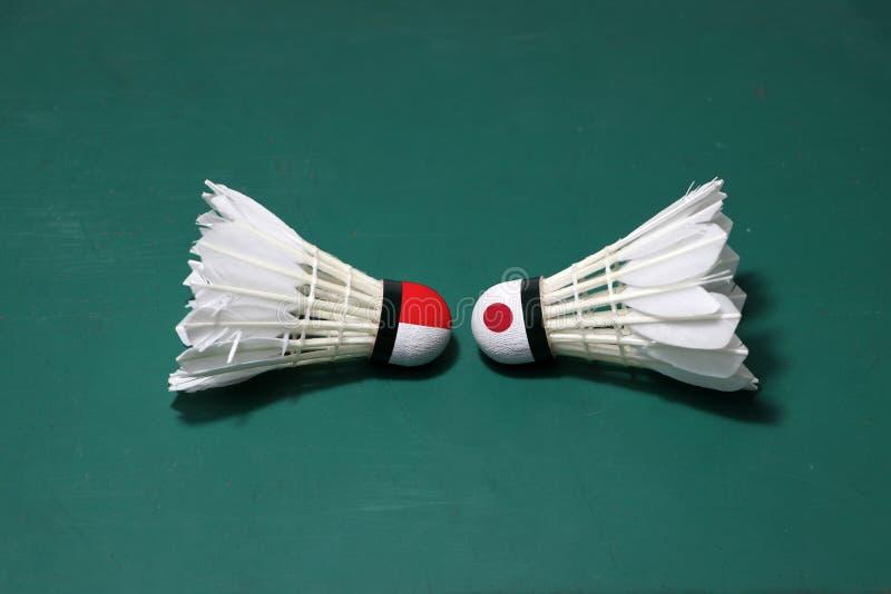 Dois usaram petecas no assoalho verde da corte de badminton com para dirigir-se Uma cabeça pintada com bandeira e uma de Indonési imagem de stock