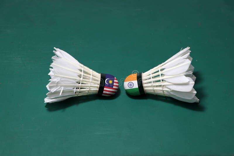 Dois usaram petecas no assoalho verde da corte de badminton com para dirigir-se Uma cabeça pintada com bandeira e uma de Malásia fotografia de stock royalty free