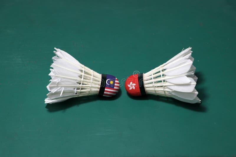 Dois usaram petecas no assoalho verde da corte de badminton com para dirigir-se Uma cabeça pintada com bandeira e uma de Malásia foto de stock royalty free