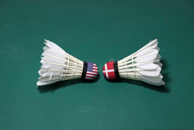 Dois usaram petecas no assoalho verde da corte de badminton com para dirigir-se Uma cabeça pintou com bandeira dos EUA e uma cabe foto de stock