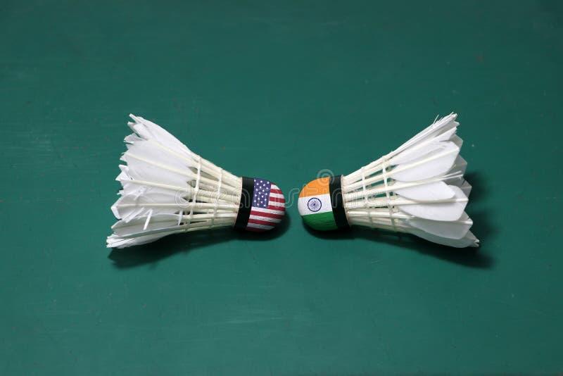 Dois usaram petecas no assoalho verde da corte de badminton com para dirigir-se Uma cabeça pintou com bandeira dos EUA e uma cabe imagem de stock