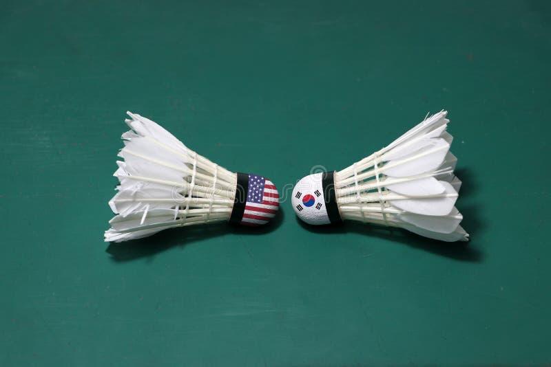 Dois usaram petecas no assoalho verde da corte de badminton com para dirigir-se Uma cabeça pintou com bandeira dos EUA e uma cabe fotografia de stock