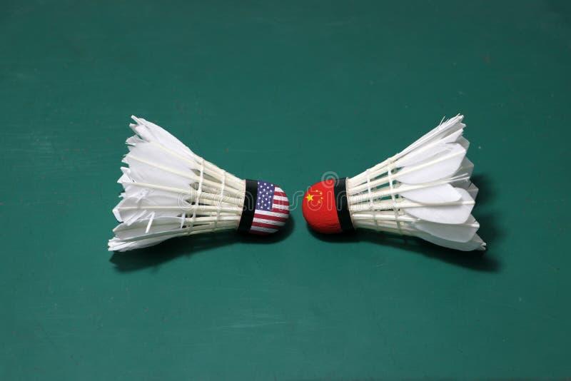 Dois usaram petecas no assoalho verde da corte de badminton com para dirigir-se Uma cabeça pintou com bandeira dos EUA e uma cabe fotos de stock royalty free