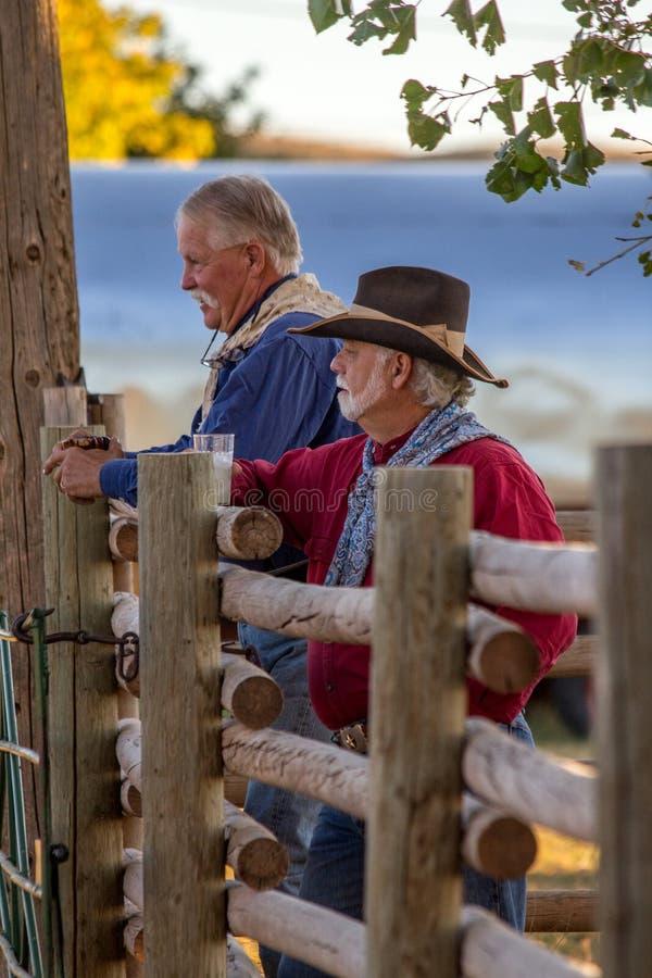 Dois vaqueiros idosos que estão pela cerca de trilho fotografia de stock royalty free