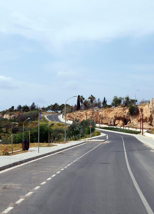 Dois vazios estrada coxo com os pavimentos e os postes de luz que curvam-se acima de um monte na distância com árvores circunvizi foto de stock