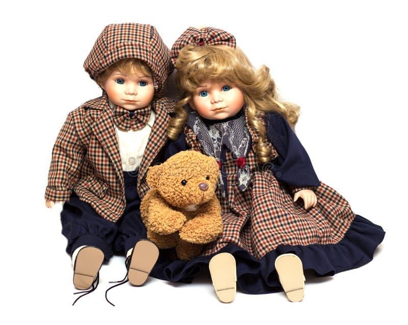 Dois velhos, bonecas cerâmicas e um urso de peluche Boneca velha da porcelana no fundo branco fotografia de stock royalty free
