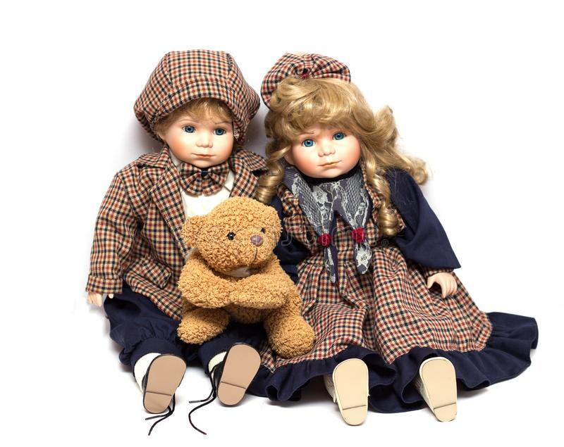 Dois velhos, bonecas cerâmicas e um urso de peluche Boneca velha da porcelana no fundo branco imagem de stock