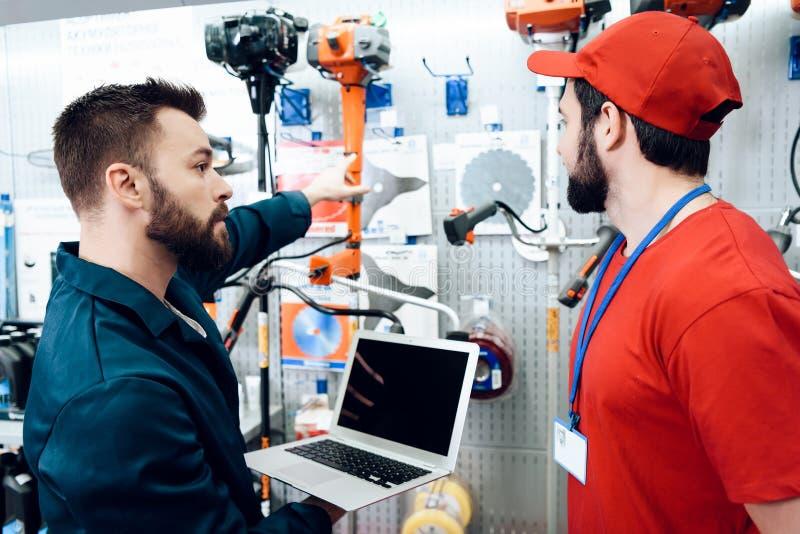 Dois vendedores estão verificando o inventário dos tooks com o portátil na loja das ferramentas elétricas imagem de stock