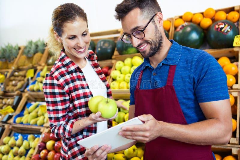 Dois vendedores novos que fazem o inventário com a tabuleta digital na loja de mantimento da saúde foto de stock royalty free