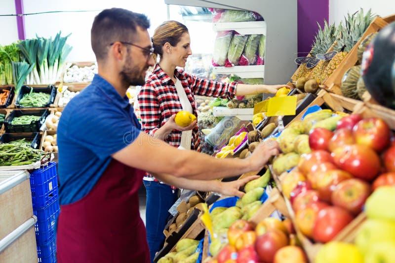 Dois vendedores novos que selecionam o fruto fresco e que preparam-se para o dia de trabalho no fruitshop fotografia de stock royalty free