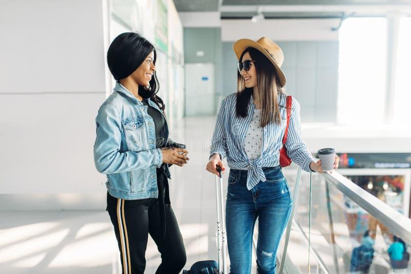 Dois viajantes f?meas com bagagem no aeroporto fotografia de stock