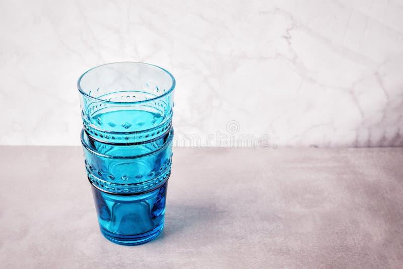 Dois vidros azuis vazios em um fundo de mármore claro Copie o espaço imagens de stock