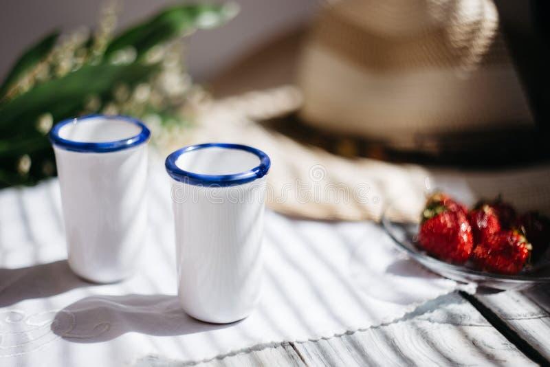 dois vidros brancos da porcelana, um chapéu, lírio do ramalhete do vale, morangos em uma tabela de madeira, luz solar imagem de stock royalty free