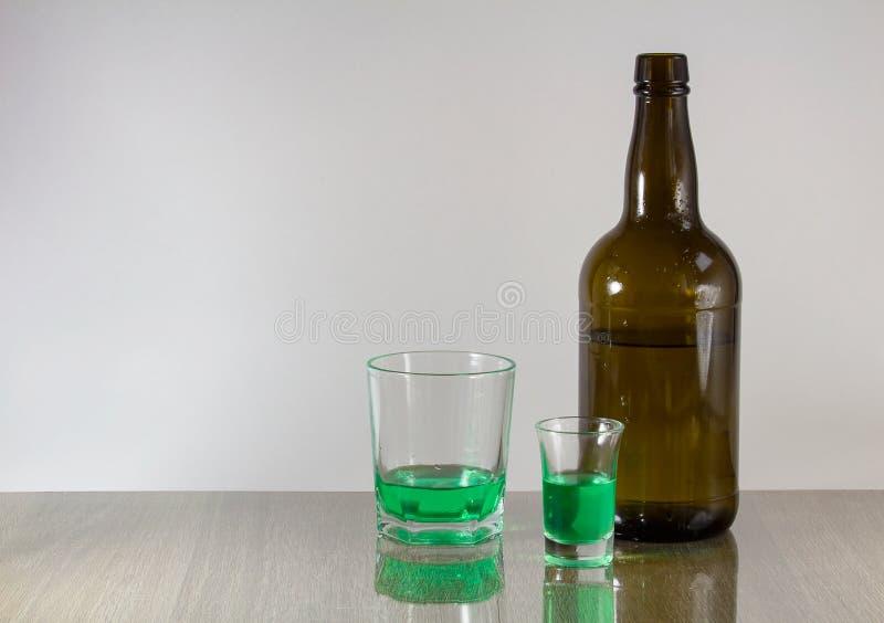 Dois vidros com álcool e a garrafa verdes no fundo branco imagem de stock royalty free