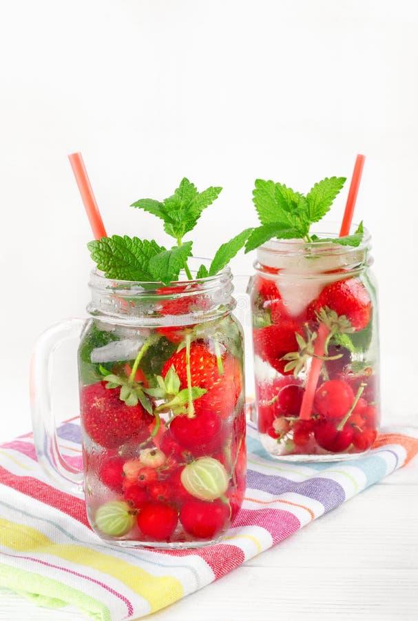 Dois vidros com bebida de bagas maduras frescas na toalha bonita fotos de stock royalty free