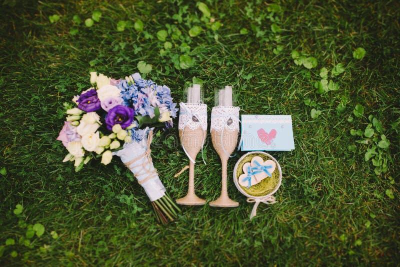Dois vidros com flores, garrafa do champanhe e alianças de casamento na grama Acessórios do casamento imagem de stock royalty free