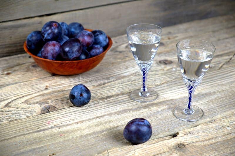 Dois vidros da aguardente da ameixa com ameixas foto de stock