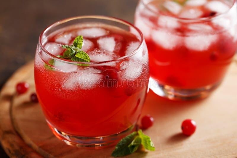 Dois vidros da bebida fria do verão com suco de arando, hortelã, cubos de gelo na tabela foto de stock