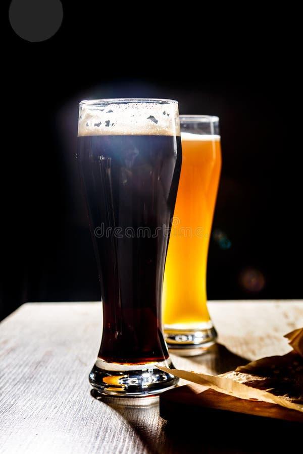 Dois vidros da cerveja que estão na tabela em um fundo escuro c fotografia de stock royalty free