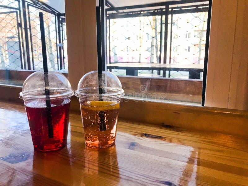 Dois vidros da limonada alaranjada de refrescamento vermelha e amarela plástica do fruto do limão do pêssego da cereja doce sabor fotos de stock royalty free