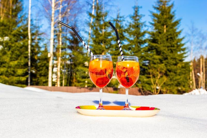 Dois vidros de Aperol frio Spritz na bandeja de neve no dia gelado ensolarado no inverno, nos pinhos e nos abeto no fundo restaur foto de stock royalty free