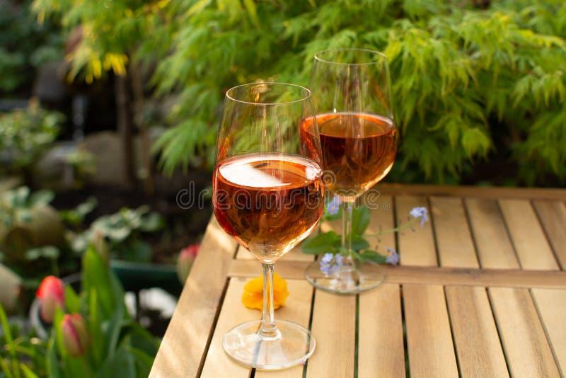 Dois vidros de vinho cor-de-rosa frios serviram no terraço exterior no jardim w imagens de stock