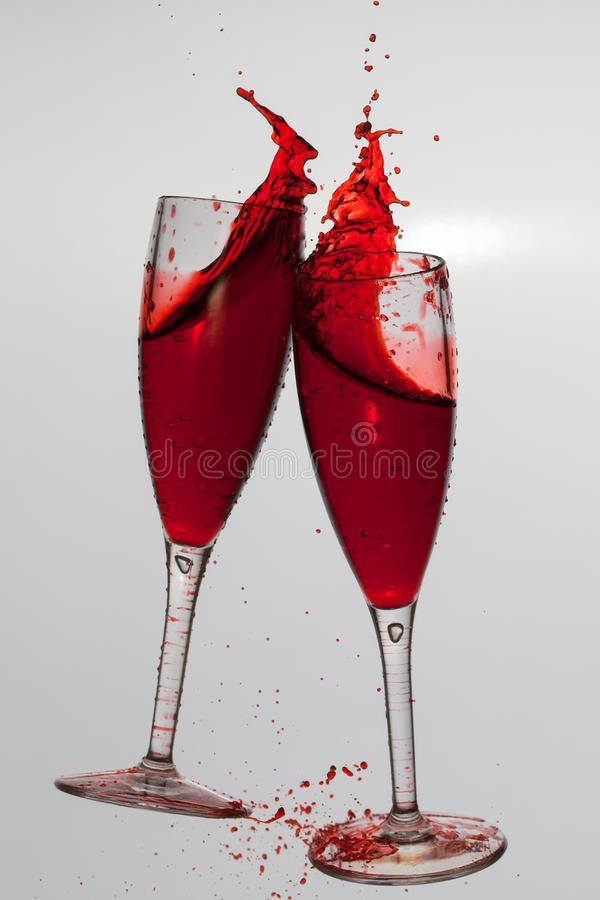 Dois vidros de vinho em brindar o gesto com espirro grande imagem de stock royalty free