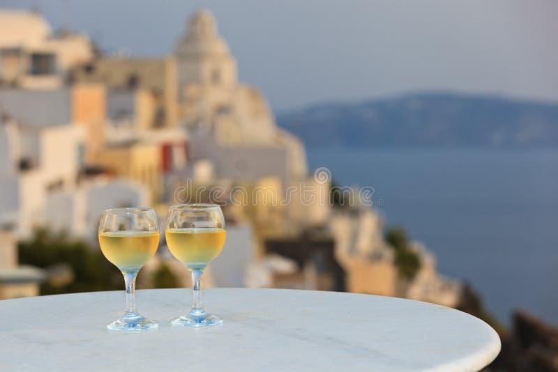 Dois vidros de vinho no por do sol Santorini imagens de stock