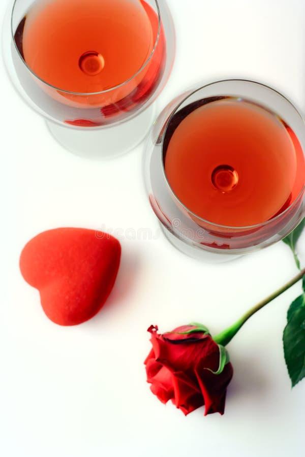 Dois vidros de vinho, uma rosa e um coração fotografia de stock