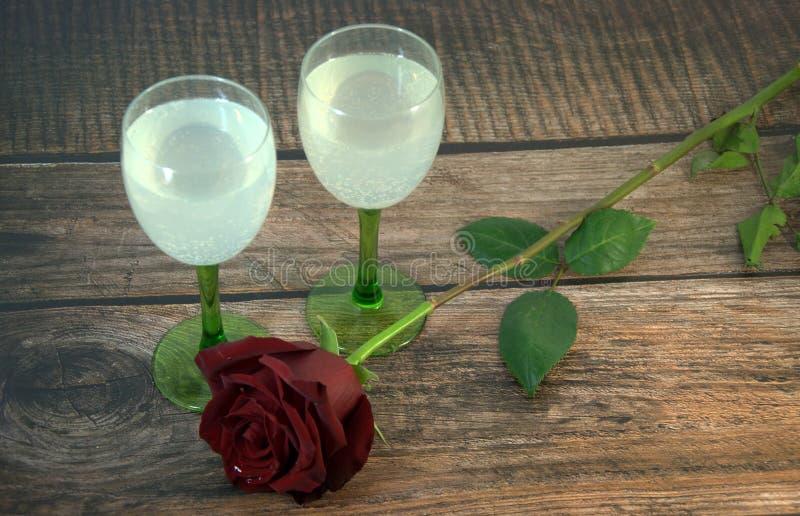 Dois vidros do champanhe e de uma rosa vermelha em uma tabela de madeira imagem de stock royalty free