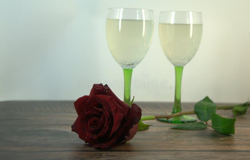 Dois vidros do champanhe e de uma rosa vermelha em uma tabela de madeira imagens de stock