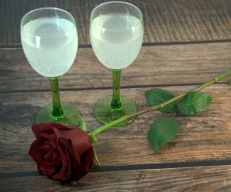 Dois vidros do champanhe e de uma rosa vermelha em uma tabela de madeira fotos de stock