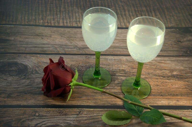 Dois vidros do champanhe e de uma rosa vermelha em uma tabela de madeira fotos de stock royalty free