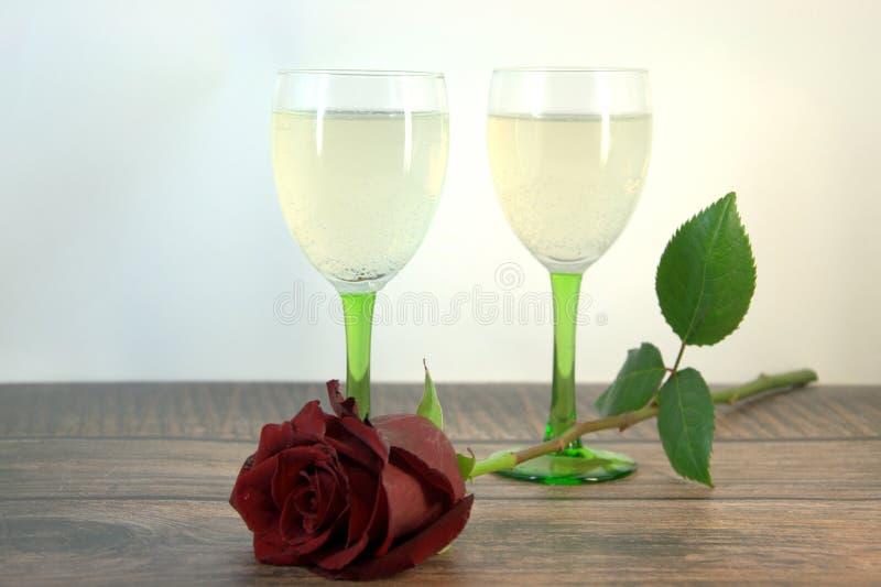 Dois vidros do champanhe e de uma rosa vermelha em uma tabela de madeira foto de stock royalty free