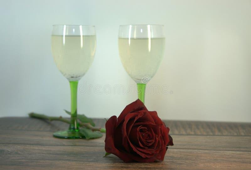 Dois vidros do champanhe e de uma rosa vermelha em uma tabela de madeira fotografia de stock
