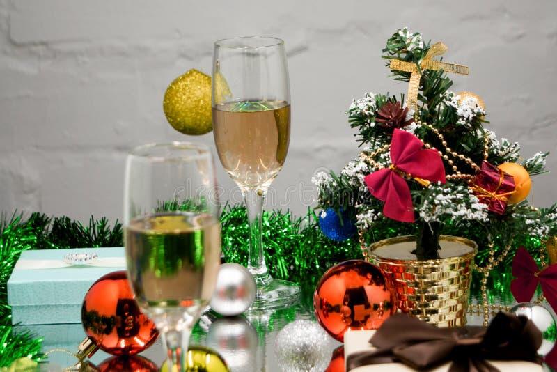 Dois vidros do champanhe no bokeh do Natal com neve, luzes, abeto e caixas de presente no fundo azul imagens de stock