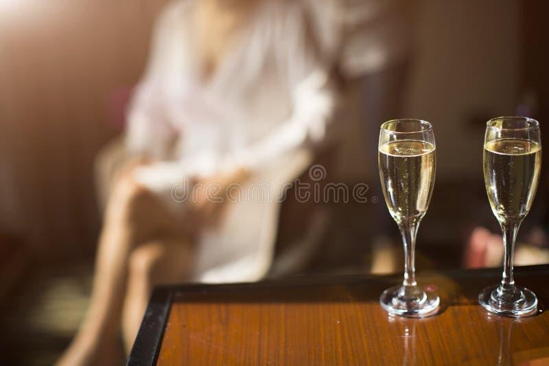Dois vidros do champanhe no fundo a silhueta fêmea imagens de stock